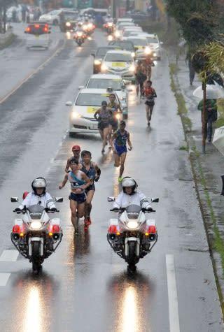 降りしきる雨の中、難所の亀割峠を駆け上がる選手たち=霧島市国分上之段