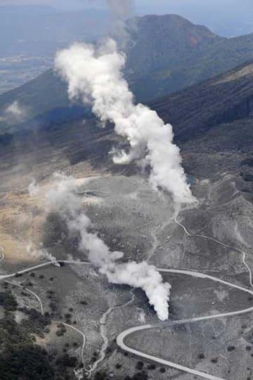 硫黄山から約500メートルの地点に出現した新たな噴気地帯(下)。付近の県道小林えびの高原牧園線の路面には傷みが確認されている=昨年4月26日、えびの市・えびの高原(共同通信社ヘリから)