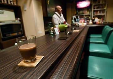 カウンターテーブルで酒を交わしながら会話を楽しむゲイバー。近年はインバウンドの来店が増加している=大阪市内