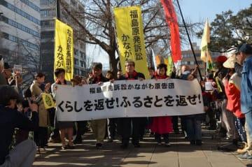横断幕を掲げて行進する原告ら=20日午前9時25分ごろ、横浜地裁前