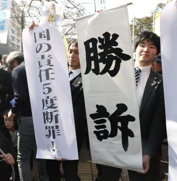 福島第1原発事故で国と東京電力に損害賠償を求めた訴訟の判決を受け、「勝訴」の垂れ幕を掲げる原告側弁護士=20日午前、横浜地裁前