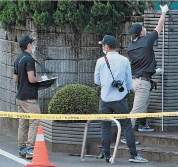 事件発生当日、現場周辺を調べる捜査員=2016年10月6日、大分市古国府