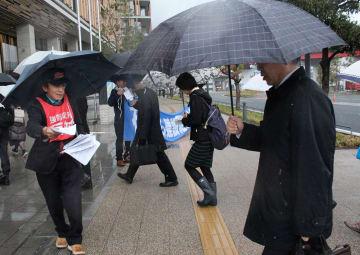 県庁職員らにダム事業中止を訴える炭谷さん(左)ら=県庁前