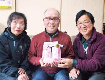 商品を手にする三嶽さん(中央)夫妻と古屋さん(右)
