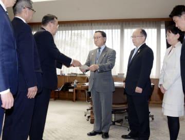 福岡県議会の議長(中央)に条例案を提出する主要4会派の議員ら=20日、福岡市