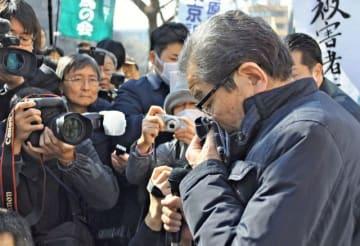 判決後、支援者らに「勝訴」を報告し、感極まる原告団長の村田弘さん=20日午前10時35分ごろ、横浜地裁前