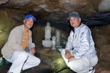 かくれ念仏の洞穴内。保存活動をする黒羽子菊哉さん(左)、黒羽子勝志さん=鹿屋市吾平町