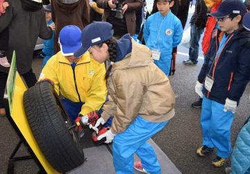 タイヤ交換を体験する児童ら