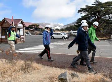えびのエコミュージアムセンター職員(左)の指示に従いながら足早に避難する訓練参加者=20日午前、えびの高原