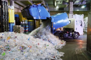 東京都港区の処理施設に運び込まれた大量のペットボトル=2017年4月