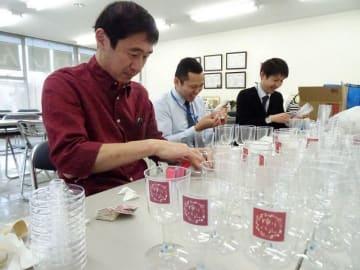ワイングラスにオリジナルのシールを貼るスタッフら=川崎市麻生区の川崎信用金庫百合丘支店