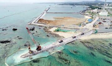 辺野古では大浦湾側に新たな護岸を造るため、海岸(手前左)に石材を敷き詰める作業が進む=2月14日午前11時40分、名護市(小型無人機で撮影)