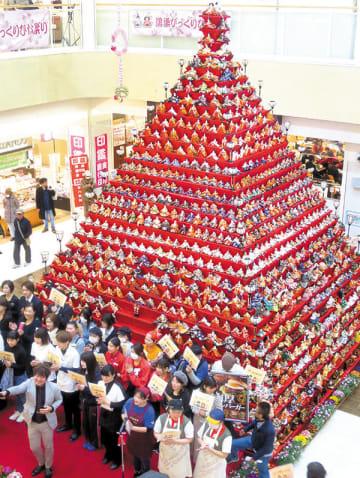 高さ7メートル、31段の日本一高いピラミッドひな壇。地元商店関係者が自身の店をPRした=20日午前、鴻巣市本町のエルミこうのす