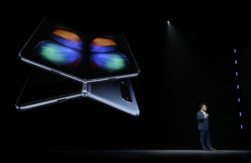 折り畳めるスマートフォン「ギャラクシーフォールド」を発表するサムスン電子幹部=20日、米サンフランシスコ(AP=共同)