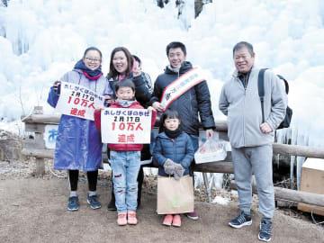 来場者10万人目となり、記念品を贈られた月井さん家族=横瀬町芦ケ久保の「あしがくぼの氷柱」