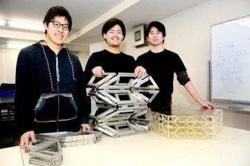 展開構造物の模型を手にする高橋鷹山さん(中央)。折りたたんだ状態から持ち上げると、右の模型のような立体になる=19日午後、東京都文京区