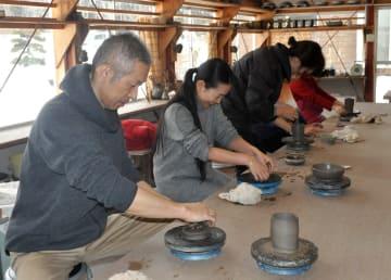 陶芸体験で思い思いに作品に取り組む参加者=17日
