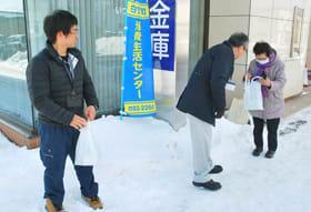 苫小牧信用金庫白老支店を訪れた人に啓発物を手渡す役場職員