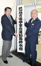 「統一地方選挙事前運動取締本部」の看板を設置する田和副署長(右)ら