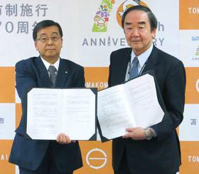 協定書を交わす岩倉市長と畑理事長(左)