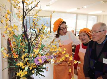 """和服を再利用して作った""""花""""をカフェ参加者と楽しむ紫原さん(左)=諫早市多良見町"""