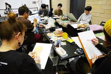 真剣な表情で制作に取り組むプロ似顔絵師たち=20日、豊中市立文化芸術センター