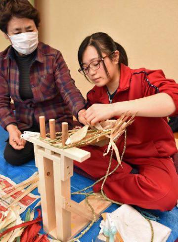 先輩の指導の下、きみがらスリッパを作る村井さん(右)