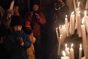 ろうそくを岩場に立て、祈りを込める子どもたち