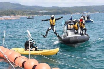 フロートを越えたカヌーに飛びかかる海上保安官=21日、名護市辺野古沖