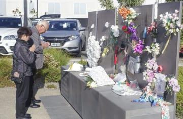 ニュージーランド地震で倒壊したCTVビル跡地で、石碑に手を合わせる遺族の鈴木喜久男さんと千鶴子さん=21日、クライストチャーチ(共同)