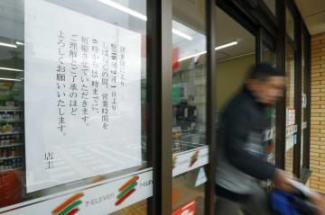 「セブン―イレブン東大阪南上小阪店」に張られた、営業時間の短縮を知らせる紙=21日午前、大阪府東大阪市