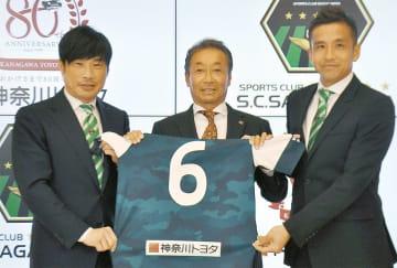 写真撮影に応じる望月代表(左)大坊常務(中)、稲本選手