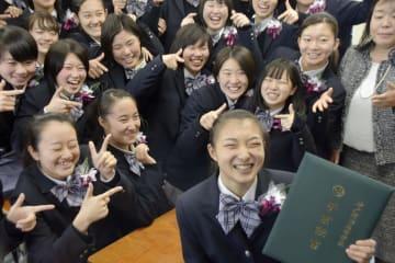 卒業証書を手にクラスメートらと笑顔を見せるフィギュアスケート女子の坂本花織=21日、神戸市
