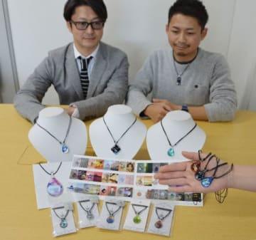 ガラス製ペンダントトップにさまざまな図柄をデザインしたノースワンの商品。背後は前原社長(左)と伊藤さん