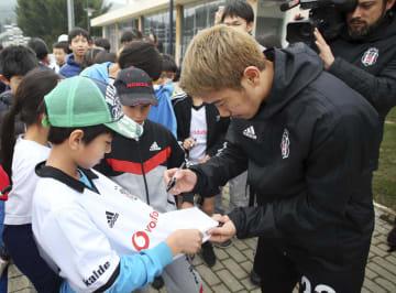 トルコ・イスタンブールの日本人学校の児童らにサインをする香川真司選手(右)=21日、イスタンブール(ベシクタシュ提供・共同)