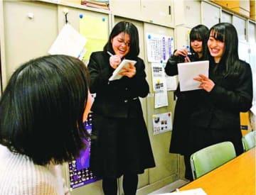 富岡西高校卒業生の教員に取材する新聞部員=阿南市の同校