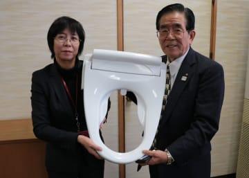 前広便座を寄贈する廣田専務理事(右)=長崎市役所