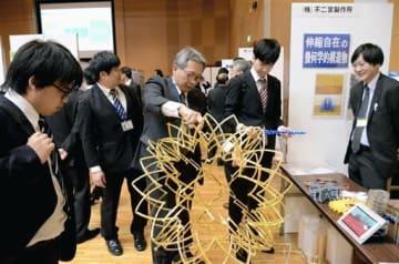 イベント会場で、企業担当者(中央)から事業内容の説明を受ける学生ら=21日、熊本市中央区