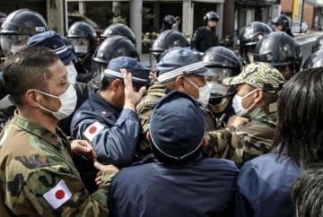 「竹島の日」式典会場周辺の右翼団体メンバーと、警備する警察官=22日午後、松江市