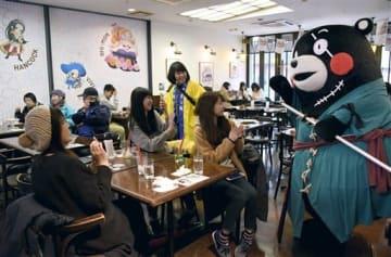 キャラクター「ゾロ」のコスプレで登場したくまモンにカメラを向ける「ワンピースカフェ」の来店客=熊本市中央区