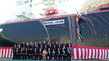 新しいLNG運搬船を背に記念撮影する関係者=長崎市、三菱重工業長崎造船所
