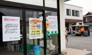 閉店の知らせが張られたAコープ小屋浦店。店の前では移動販売車が客を迎えていた(22日)