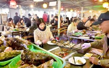 大勢の来場客でにぎわった「出張カキ小屋 牡蠣奉行」=2月22日、福井県福井市のハピテラス