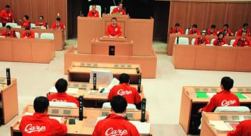 沖縄市で春季キャンプ中の広島を盛り上げようと赤いジャンパーを着て議会に臨む全市議と執行部=19日、沖縄市議会