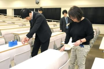 試験会場の机に受験番号を貼る職員=22日、新潟市西区の新大五十嵐キャンパス