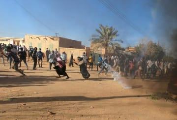スーダンの首都ハルツームで、治安部隊が発射した催涙弾から逃げるデモ参加者ら=1月20日(ロイター=共同)