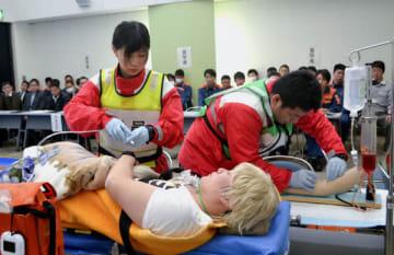 【医師を通じて看護師と連携し処置を施す救命士ら=亀山市野村4丁目の消防本部庁舎で】
