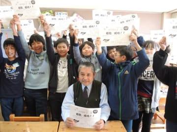 大塚校長(手前)が作った号外を手に着陸成功を喜ぶ児童たち