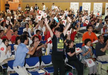 内村選手の連覇が決まった瞬間、万歳をする父和久さん(中央)と、歓喜の声を上げる市民=11日午前6時39分、諫早市小船越町、市中央体育館