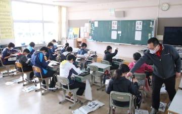 複式学級で書道を指導する教諭(右)。児童のうち手前の縦2列が5年生、奥3列が6年生=対馬市、西小